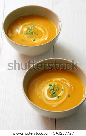 Butternut squash soup with cream on white wooden table - stock photo