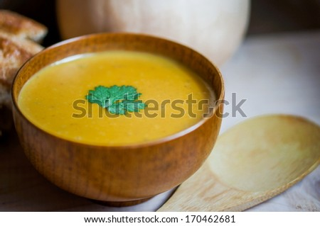 Butternut squash soup with homemade bread on wooden background - stock photo