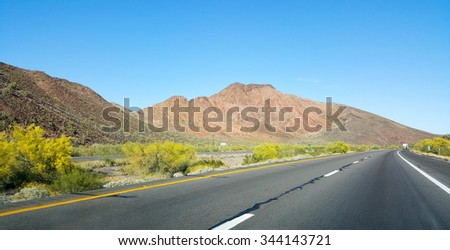 Buttes, hills and low rise mountains along Interstate-10 east of city of Quartzsite.in Arizona desert covered with drought and extreme heat resistant vegetation.