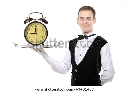 Buttler holding a silver tray with a alarm clock on it - stock photo