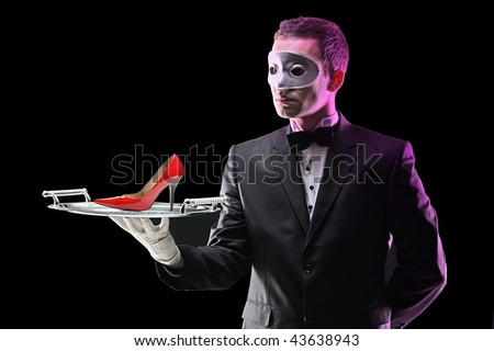 Buttler with a mask holding a tray with high heel on it - stock photo