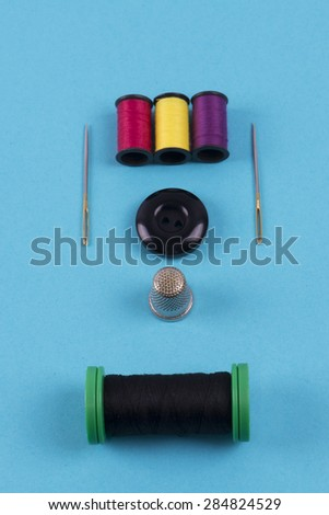 Button with needle, thimble and thread colors on a blue background - stock photo