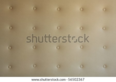 Buttoned beige leather background exposed to soft light - stock photo