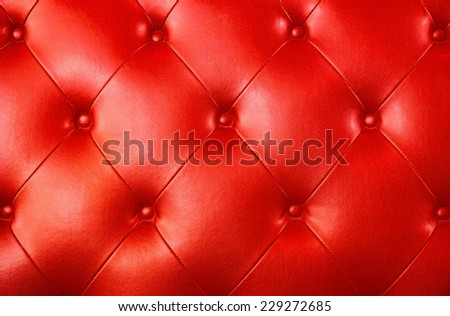 Buttoned on the red Texture leather background - stock photo
