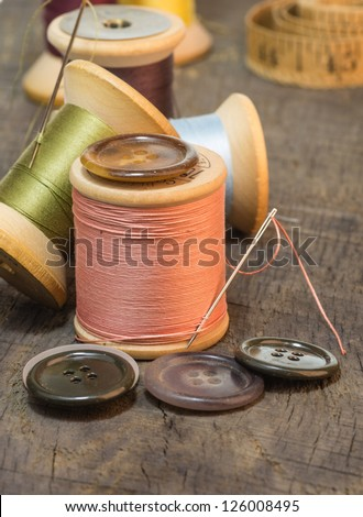 Buttons and needles with spools of sewing thread - stock photo