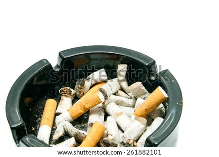 butts in black ashtray on white background closeup - stock photo