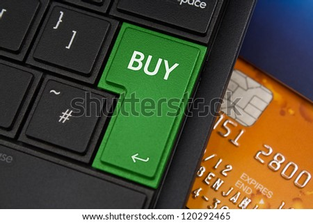 Buy Enter Key on a modern laptop qwerty keyboard with bank smart card underneath to represent on-line shopping - stock photo