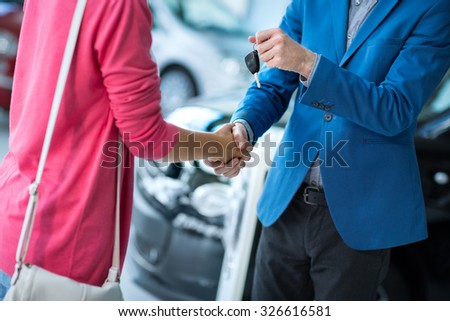 Buy new car,   woman receiving car key from salesman