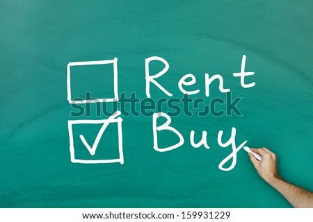 Buy not rent concept on green blackboard - stock photo