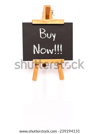 Buy Now. Blackboard with text and easel. Photo on white background with shadow and reflection. - stock photo