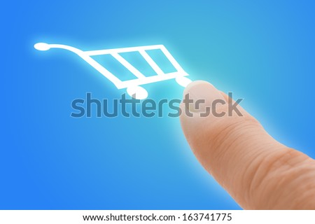 Buy Now Touch Screen Finger Pointing to Shopping Cart Icon on Futuristic Computer Tablet