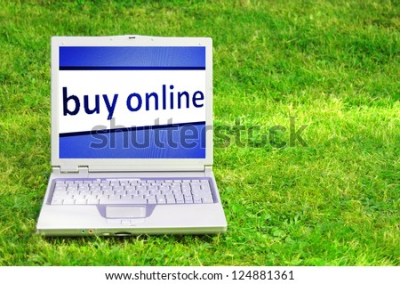 buy online or ecommerce concept with laptop in green grass - stock photo