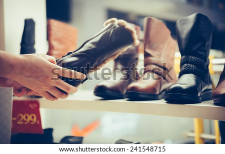 buy shoes in a footwear shop. - stock photo