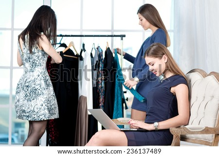 Buying a new wardrobe. Shopaholic girl makes online shopping a laptop while her friend choose the dress on a hanger. Girls having fun together doing shopping - stock photo
