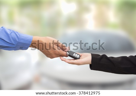 Buying Car.Businessman giving a key car to businesswoman on blur background.
