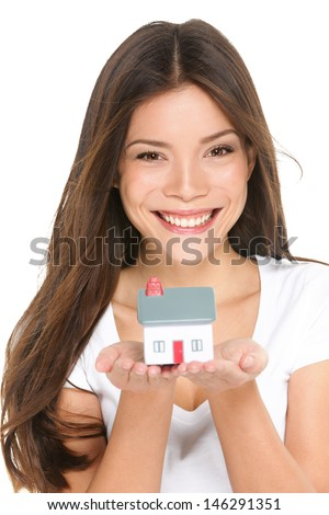 Buying new home concept - woman holding mini house. House mortgage and happy home owner conceptual image with multi-ethnic Asian Chinese / Caucasian female model isolated on white background. - stock photo