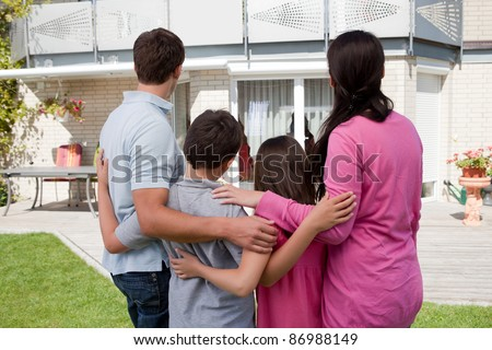 Buying new home - Family standing in front of their new house