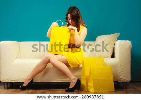 Buying retail sale concept. Fashionable girl yellow dress high heels sitting on couch with shopping bags