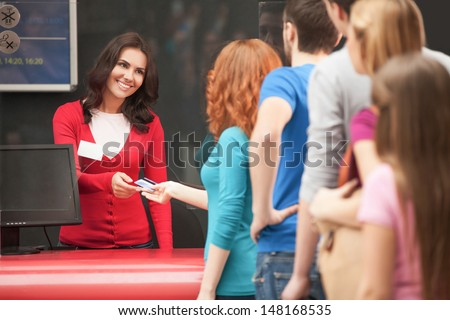 Buying the movie tickets. Young people waiting in line to buy the movie tickets - stock photo
