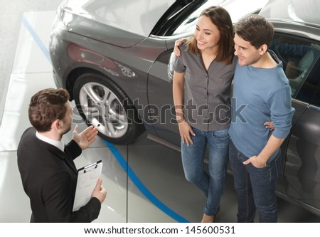 Buying their first car together. High angle view of young car salesman standing at the dealership telling about the features of the car to the customers - stock photo