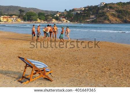 BUZIOS, BRAZIL - OCTOBER 16, 2014: Teenagers play soccer at Geriba beach in Buzios, state of Rio de Janeiro in Brazil. Brazil had 5.17 million visitors in 2012. - stock photo