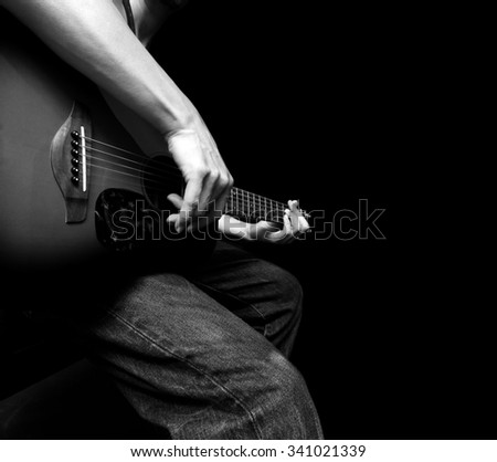BW photo of guitarist hands playing acoustic guitar isolated on black - stock photo