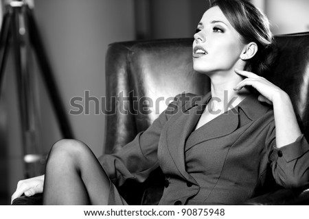 BW portrait of a young business woman in an office - stock photo