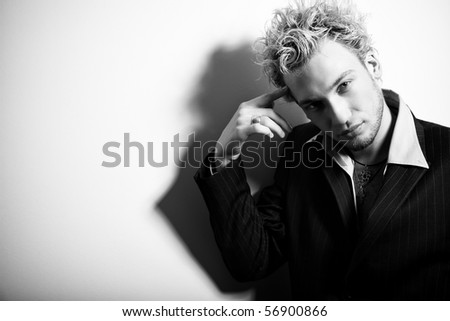 BW portrait of handsome stylish blond man in suit pointing finger at his head - stock photo