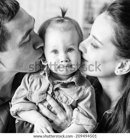 BW portrait of lovely family together at home. Mother and father kissing his year-old daughter - stock photo