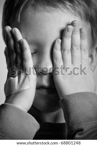 BW portrait of sad crying little boy covers his face with hands. One hand with medical plaster. - stock photo