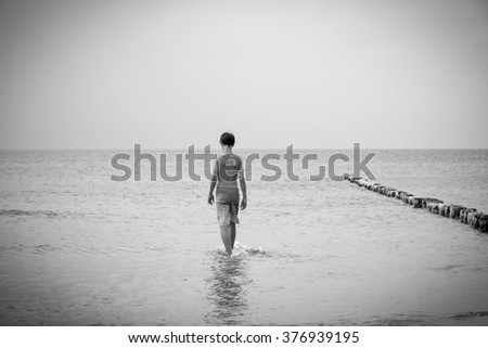 bw shot of a teenage boy who is walking into the sea - stock photo