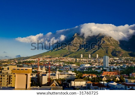 By a beautiful summer, a big cloud has formed on the Table Mountain in Cape Town, South Africa. - stock photo