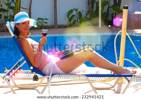 By the pool with a glass of red wine ; Young woman relaxes by the pool with a chat and a glass of red wine - stock photo