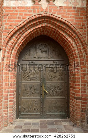 BYDGOSZCZ, POLAND - APRIL 6, 2016. Entrance door to the Cathedral Church in Bydgoszcz, Poland, with seven panels depicting various scenes, and brick wall.