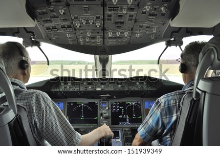 BYDGOSZCZ, POLAND - AUGUST 4: Pilots in the cockpit Boeing 787 Dreamliner preparing for departure from airport on August 4, 2013 in Bydgoszcz, Poland. Training flight from Bydgoszcz to Wroclaw.  - stock photo