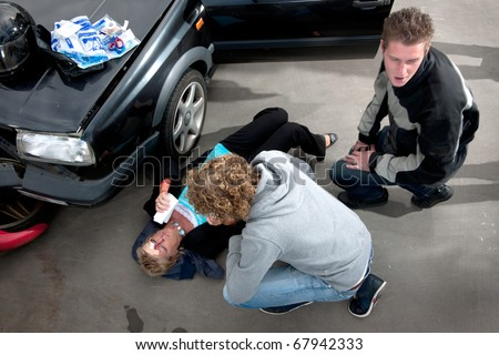 Bystander providing first aid to an injured woman lying on the ground, bleeding, after a car crash, with a first aid kit on the hood of her damaged car - stock photo