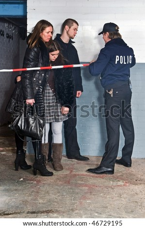 Bystanders being kept at a distance by a policeman setting the perimeter of a crime scene with cordon tape - stock photo