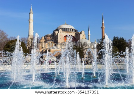 Byzantine architecture of the Hagia Sophia (The Church of the Holy Wisdom or Ayasofya in Turkish) and a park with fountain tranquil scenery in Istanbul, Turkey - stock photo