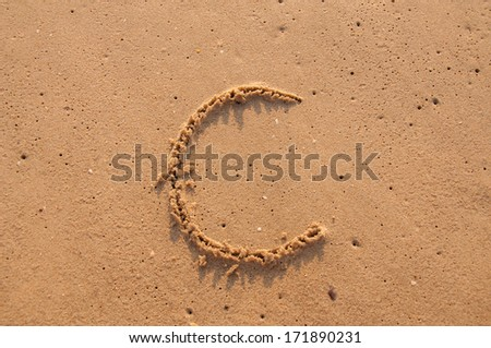 C text written in the sandy on the beach - stock photo