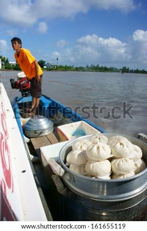 CA MAU, VIET NAM- JUNE 29: Food vendor by boat selling dumpling on water, this is culture of mekong delta, Ca Mau, Viet Nam, June 29, 2013