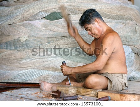 CA MAU, VIET NAM- JUNE 29. Portrait of the man with carpentry tool bore a hole in section of a tree trunk, at him back, there are some fishing net roll to fisherman catch fish. June 29, 2013