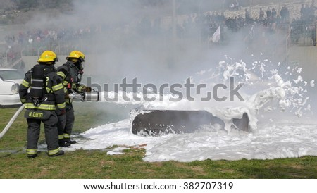 CAABIYA, ISRAEL - FEBRUARY 10, 2016: Firefighter from Northern Israel Fire Brigade dispense snow white foam on burning container during drill, to increase awareness of Arab kids to risks of fire