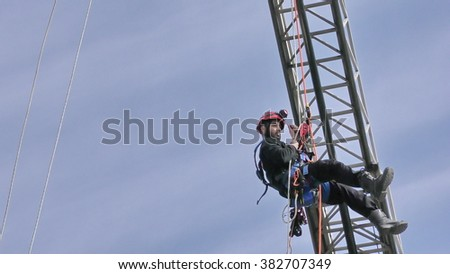 CAABIYA, ISRAEL - FEBRUARY 10, 2016: Firefighter from Northern Israel Fire Brigade drop from crane during drill under blue sky, to increase awareness of Arab kids to risks of fire
