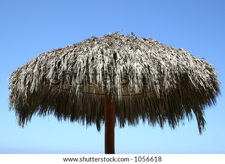 Cabana umbrella with a clear blue sky - stock photo