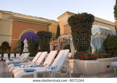 Cabanas and chaise lounges at a colorful tropical resort swimming pool - stock photo