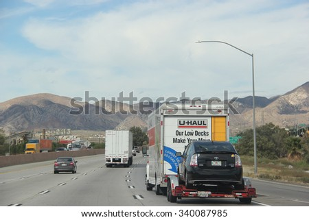 Cabazon, California, USA - October 14, 2015: U-Haul Truck is towing a car on a freeway. U-Haul, an American moving equipment and storage rental company, provides trucks for rental suitable for moving. - stock photo