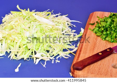 Cabbage and parsley finely chopped with a knife on a cutting board - stock photo