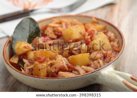 Cabbage and potato stew. Selective focus on a front edge of the dish - stock photo