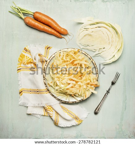 cabbage carrots salad in plate with fork and ingredients, top view composing - stock photo