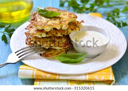 Cabbage fritters with cream sauce on a white plate.